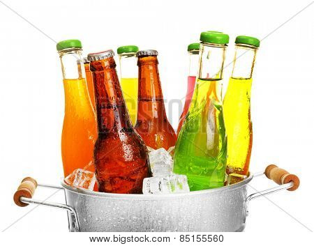 Glassware of different drinks in metal bucket with ice cubes isolated on white