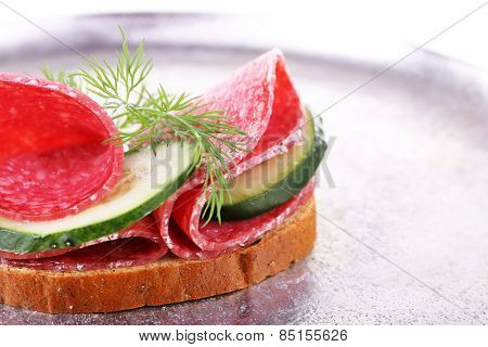 Sandwich with salami and cucumber on metal tray background