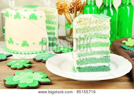Still life with sliced cake and green beer for Saint Patrick's Day on wooden table and blurred background