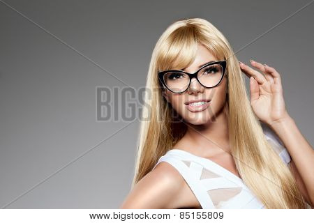 Beauty young woman luxury long blond hair in glasses Haircut, fringe Girls fresh healthy skin, makeup lips, eyelashes, manicured nails shiny. Fashion model in spa care salon Sexy trendy hairstyle look