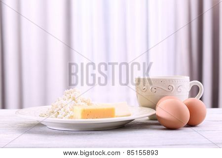 Eggs and dairy products on wooden table on curtain background