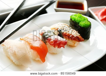 Sushi on plate on wooden table background