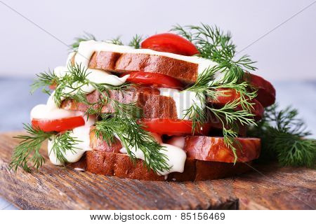 Sandwich with sausage, tomato and mayonnaise on cutting board, closeup