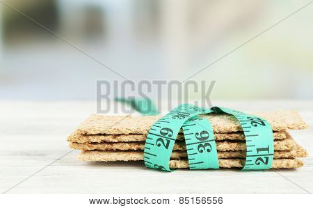 Fresh crispbread with measuring tape, on wooden table- diet concept