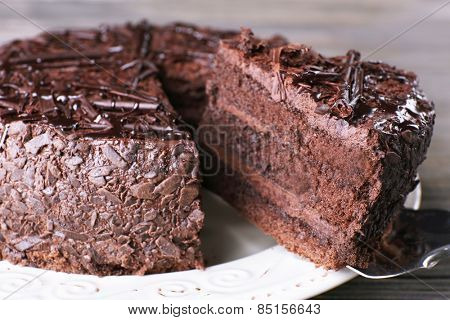 Sliced tasty chocolate cake in plate with blade on wooden table background, closeup