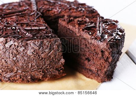 Sliced tasty chocolate cake in sheet of parchment on wooden table, closeup