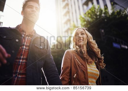 couple walking while holding hands in los angeles with lens flare and selective focus