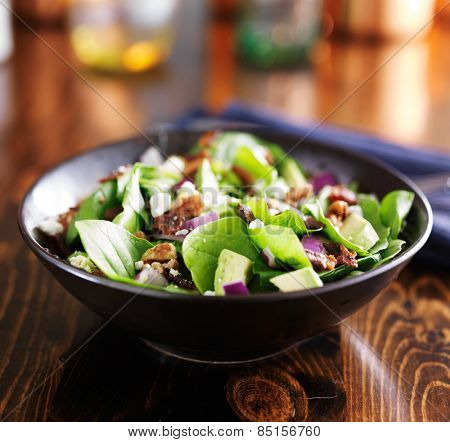 spinach and avocado chopped salad in stoneware bowl