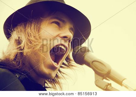 Young man with long hair and hat singing, shouting to microphone. Vintage, music, hipster.