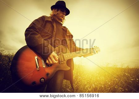 Young man playing on the guitar outdoors. Vintage, music concept