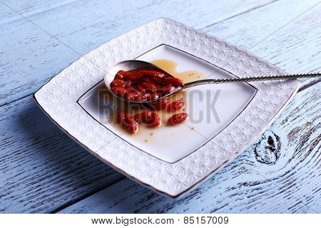 Goji berry jam in spoon on plate on wooden background