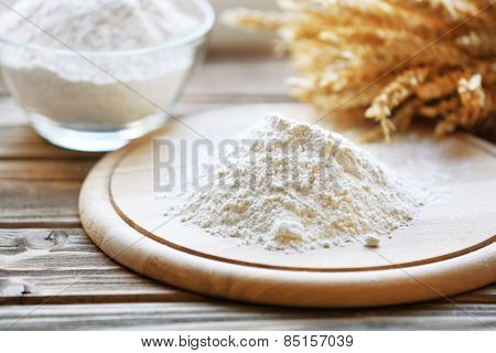 Pile of flour on cutting board with glass bowl, closeup