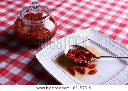 Goji berry jam in spoon on plate with jar on table close up
