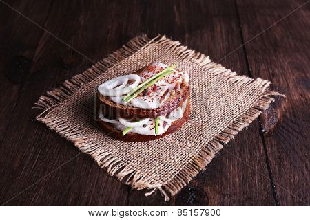 Sandwiches with lard and onion on sackcloth on table close up