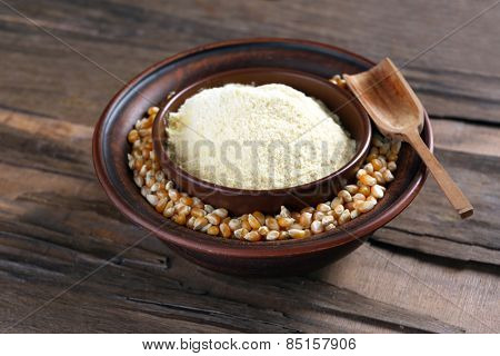 Flour and corn grains in bowls with spoon on wooden background