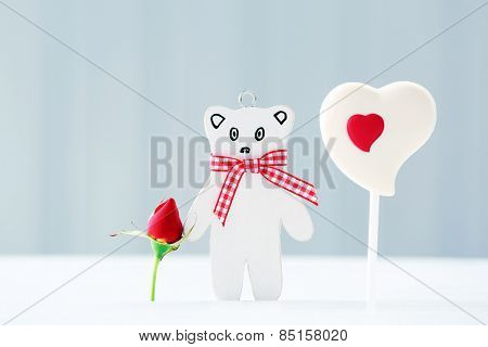 Sweet heart with toy bear on table on light background