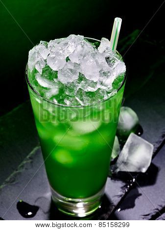 Green drink  with crushed ice on dark background.