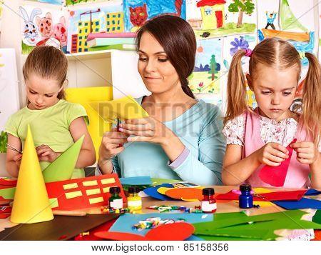 Children  with teacher cutting out scissors paper in preschool.