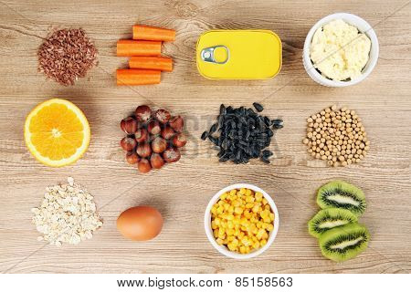 Various food products containing vitamins on wooden background