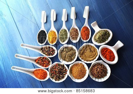 Different kinds of spices in ceramics spoons, close-up, on color wooden background