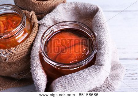 Homemade jars of fruits jam in burlap pouches on color wooden planks background