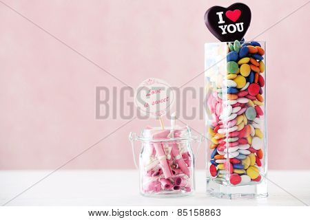 Colorful sweets with inscription in vase on table on color background