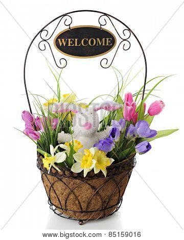 An adorable toy rabbit surrounded by colorful spring flowers, all in a wire basket with a welcome sign on the handle overhead.