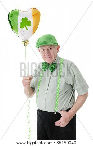 A senior Irish man proudly wearing his green while holding a shamrock adorned tri-colored, heart-shaped balloon.  On a white background.
