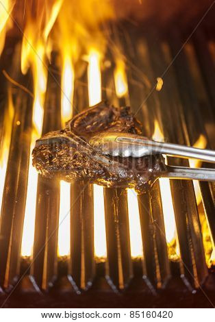 T-bone steak on the barbecue being turned around