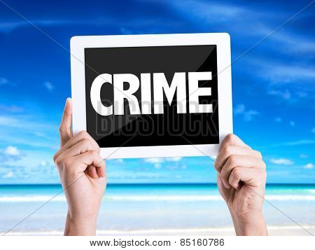 Tablet pc with text Crime with beach background