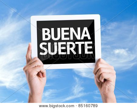 Tablet pc with text Good Luck (in Spanish) with sky background
