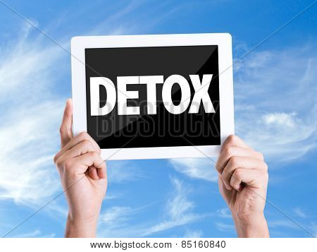 Tablet pc with text Detox with sky background