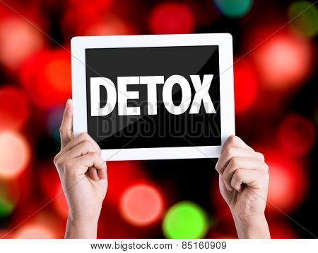 Tablet pc with text Detox with bokeh background