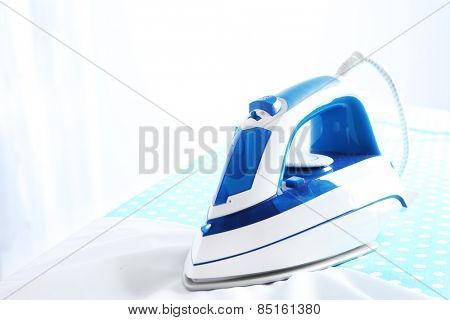 Iron on ironing board on light background