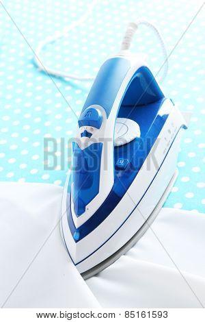 Iron on ironing board close-up