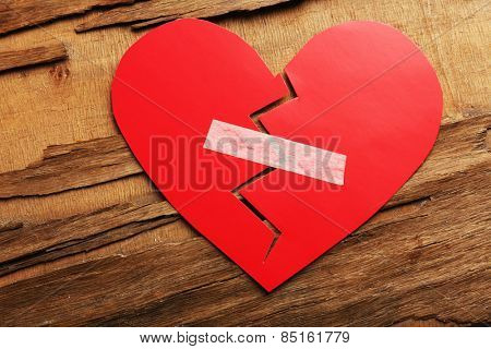 Broken heart with plaster on rustic wooden table background