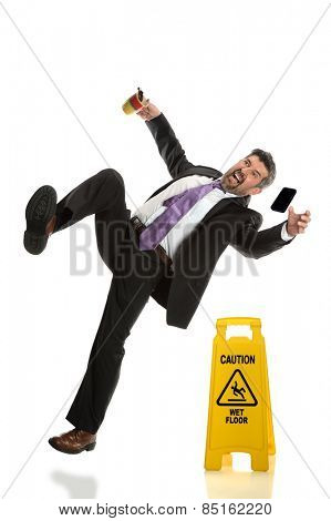 Hispanic businessman falling next to wet floor sign isolated over white background