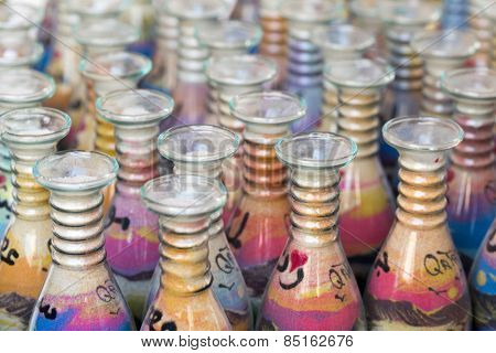 DOHA, QATAR - MARCH 8, 2015: Sand-filled glass bottles sold as souvenirs of Qatar in the Souq Waqif shopping area.