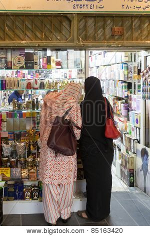 DOHA, QATAR - MARCH 8, 2015: Shoppers look at the goods in the covered part of Souq Waqif, a popular tourist attraction