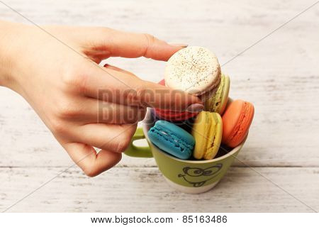 Female hand taking tasty colorful macaroons from cup on color wooden background