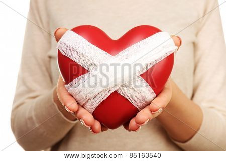 Woman holding bandaged heart close up