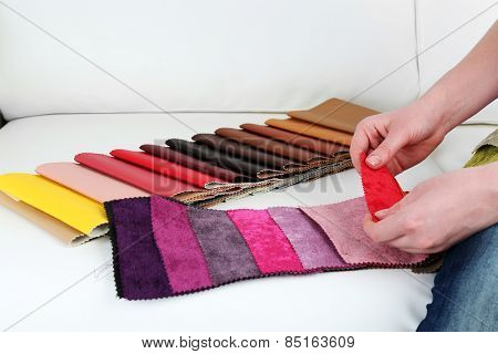 Woman sitting on sofa and chooses scraps of colored tissue