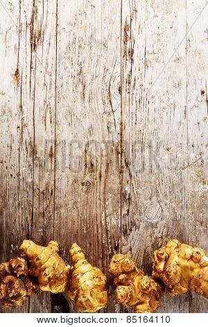Fresh organic topinambur on wooden background, Jerusalem artichoke