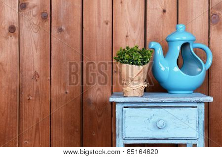 Interior design with decorative pot and plant on tabletop on wooden planks background