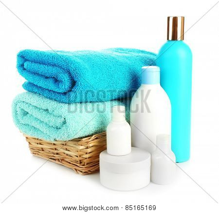 Towels in wicker basket with shampoo bottles isolated on white