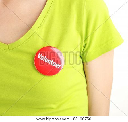 Round volunteer button on shirt of girl isolated on white