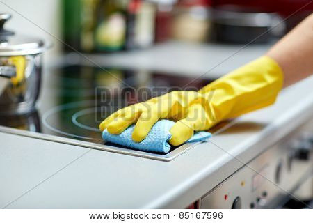 people, housework and housekeeping concept - close up of woman hand in protective glove with rag cleaning cooker at home kitchen