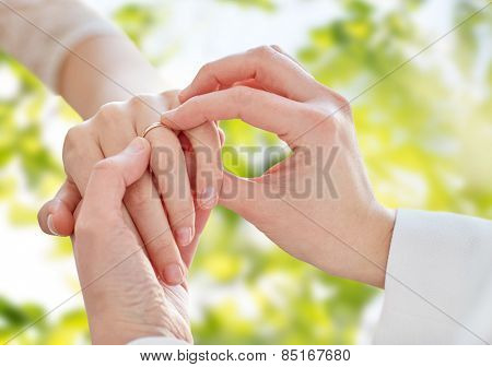 people, homosexuality, same-sex marriage, summer and love concept - close up of happy lesbian couple hands putting on wedding ring over green tree leavers background