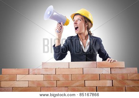 Woman builder with loudspeaker on white