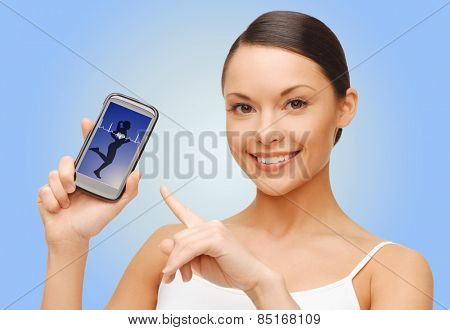 people, technology, health control and sport concept - happy young woman pointing finger to smartphone screen showing human cardiogram over blue background
